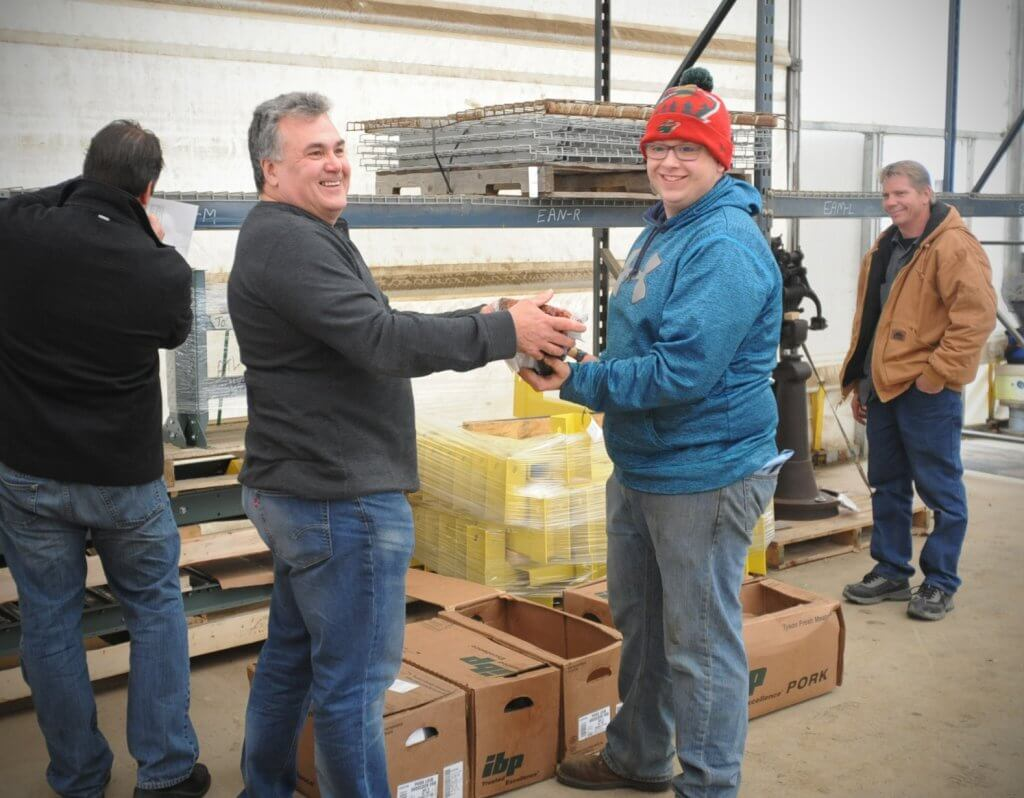 Frank Sterner, second from the left, hands a ham to Ethan Heimkes, second from the right, for his holiday bonus. Also pictured are Ed Salonek, left, and Brian Springer, right.